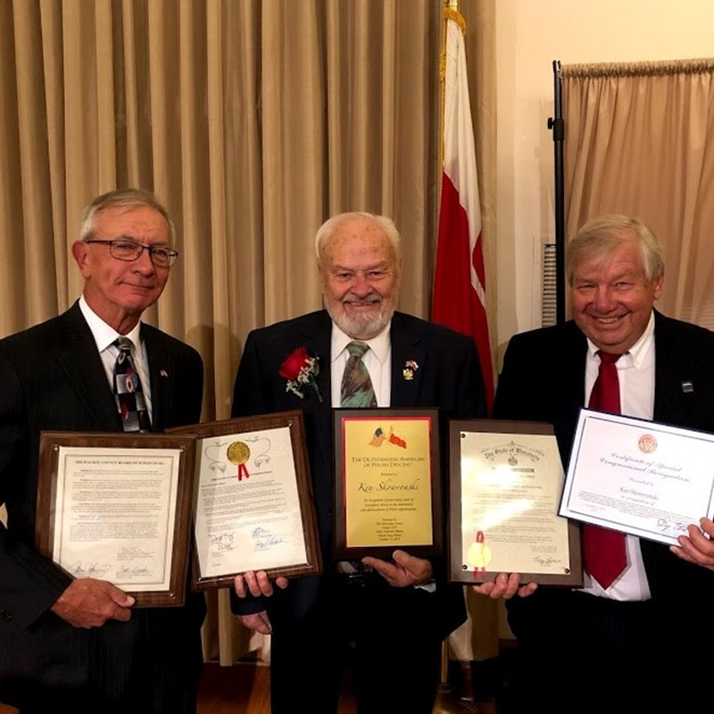 L to R:  Banquet co-chairman David Zepecki and Terry Witkowski assisting Rep. Skowronski in displaying the plaques presented during the banquet.