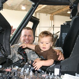 CPT Grant and his son, Kaleb, exploring the cockpit of a UH60 Blackhawk Helicopter