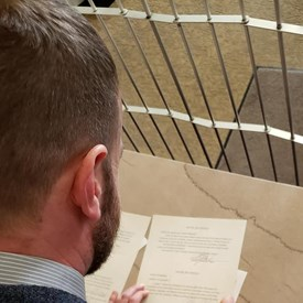 Adam signing his oath of office