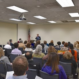 Vice Chair Gregory Begg addresses members and guests at our April meeting.   Photo Credit: Betsy Bacot-Aigner