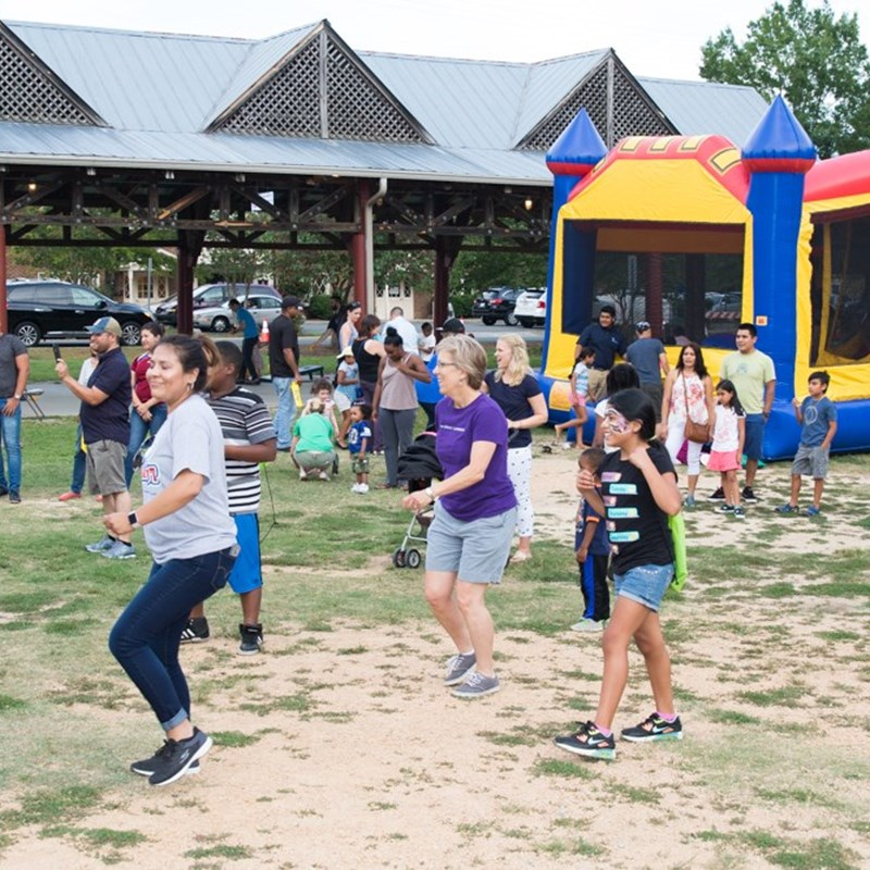 Lydia does the cha cha slide with officers and participants in National Night Out.