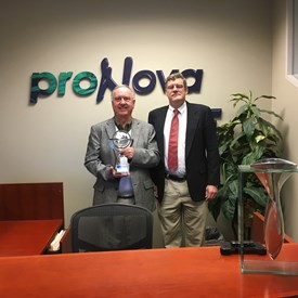 Dr. Eric Maidla, the president and part owner of TDE Petroleum Data Solutions, Inc., poses with Malcolm and the 2017 World Oil Award for Innovation.