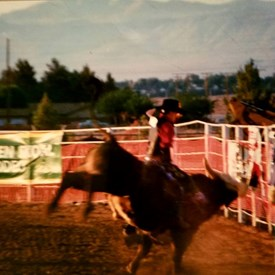 Bill Polyniak bull riding at a rodeo