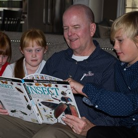 Dave at home, reading with his grandchildren.
