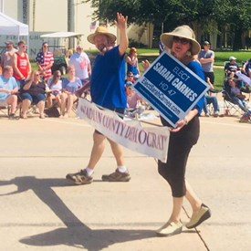 Jeramy and Sarah Carnes hold the banner at the Freedom Festival Parade on Independence Day (July 4, 2018).