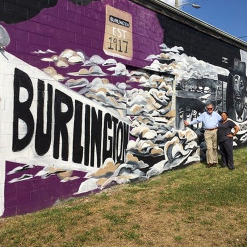 Duane Grieve, executive director of the East Tennessee Community Design Center, and board member Dasha Lundy pose for a photo by the mural celebrating the Burlington community May 28, 2019.