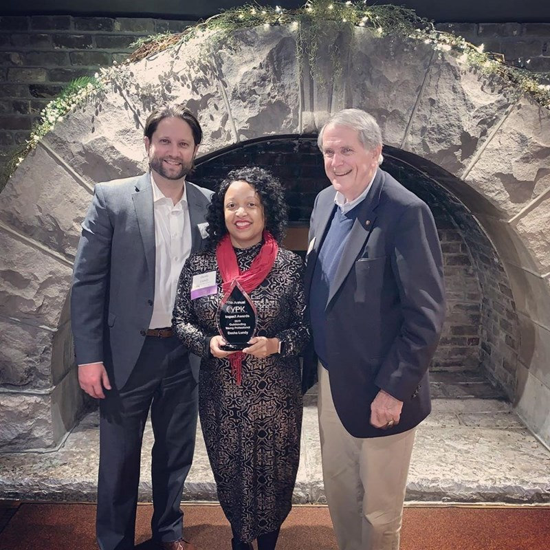 Dasha Lundy accepting an Impact Award. Pictured here with former vice-mayor Duane Grieve and Nathan Honeycutt of McCarty Holsapple McCarty.