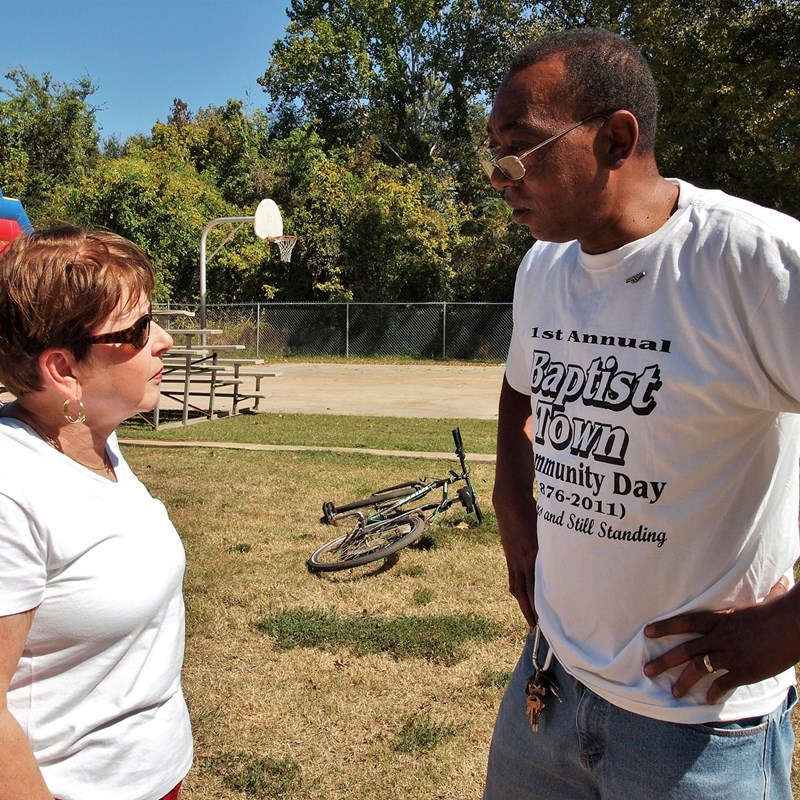 Carolyn speaks to a resident at Baptist Town's community day event.